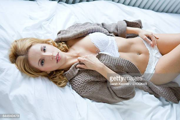 Young woman in cardigan and lingerie lying on bed
