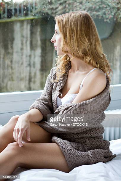 Young woman in cardigan sitting on bed