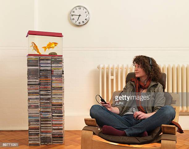 Young woman in chair listening to music
