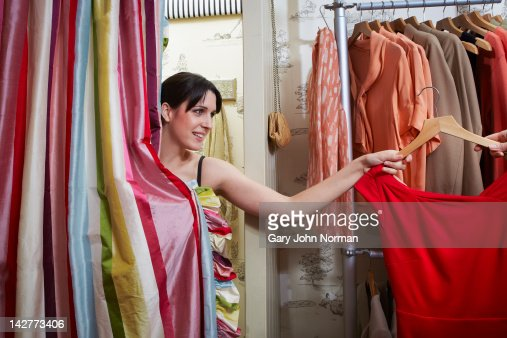 Young woman in changing room of boutique shop : Stock Photo