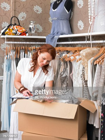 Young woman in clothes shop taking merchandise from cardboard box and writing on clipboard