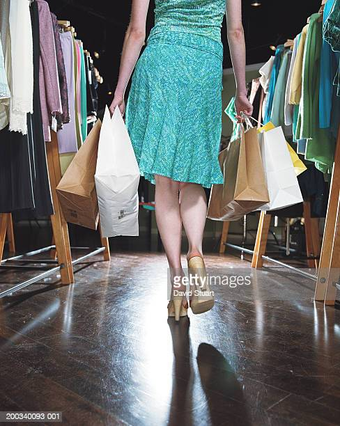 Young woman in clothing store, carrying shopping bags, rear view
