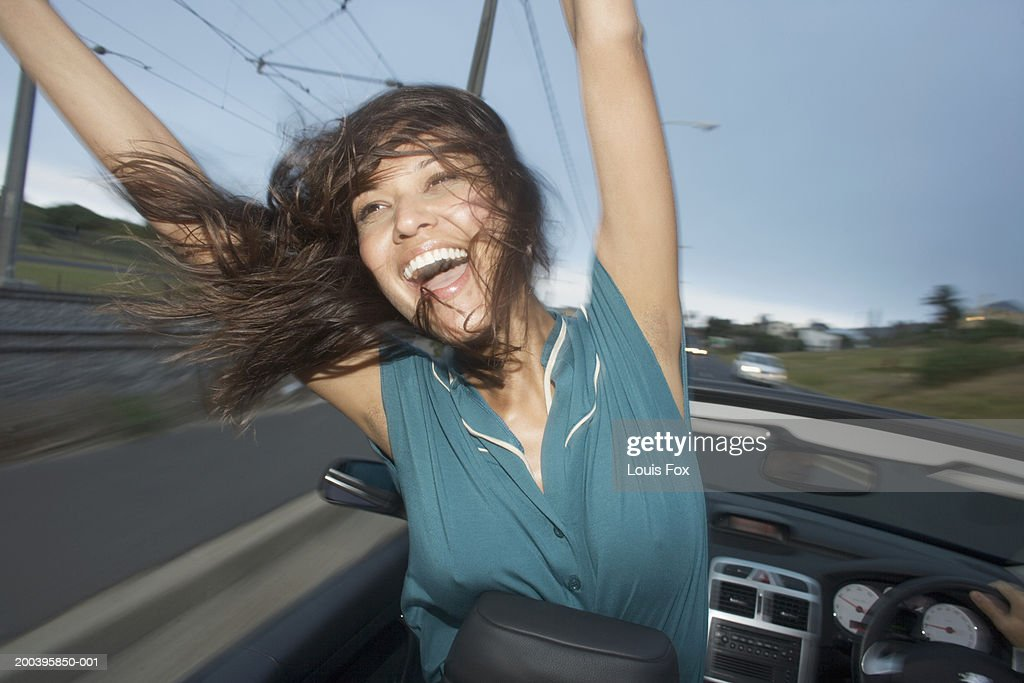 Young woman in convertible car, arms raised, smiling : Stock Photo