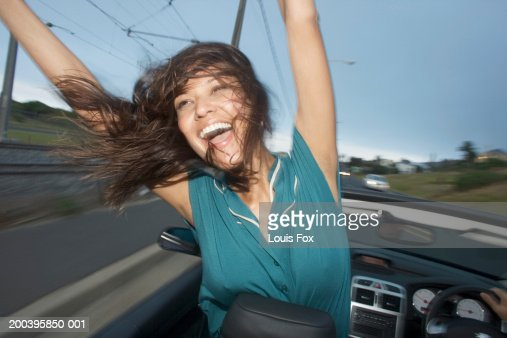 Young woman in convertible car, arms raised, smiling : Foto stock