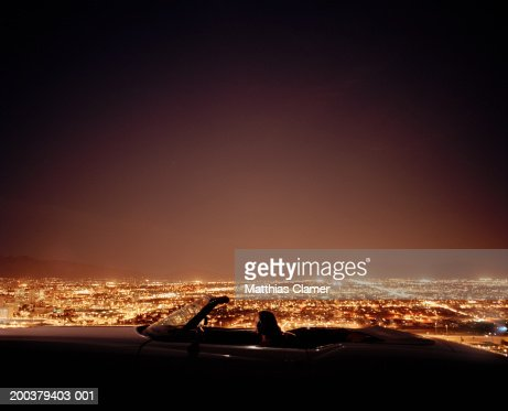 Young woman in convertible overlooking city, side view