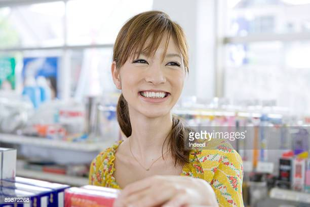 Young woman in convinient store, smiling