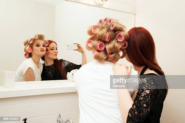 Young woman in curlers and friend taking selfie