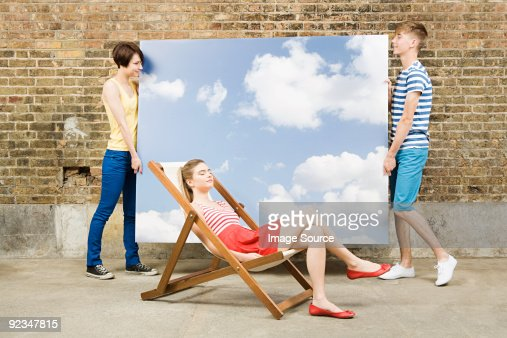 Young woman in deckchair and others with sky backdrop