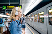 Beautiful young blond woman in denim shirt with earphones, standing at the underground platform, waiting to enter a train