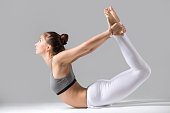 Young attractive woman practicing yoga, stretching in Bow exercise, Dhanurasana pose, working out wearing sportswear, white pants, gray top, indoor full length, isolated against grey studio background