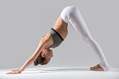 Young attractive woman practicing yoga, standing in Downward facing dog exercise, adho mukha svanasana pose, working out wearing sportswear, white pants, indoor full length, grey studio background