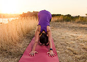 Young woman in downward facing dog pose, in sunset by the river, city in distance