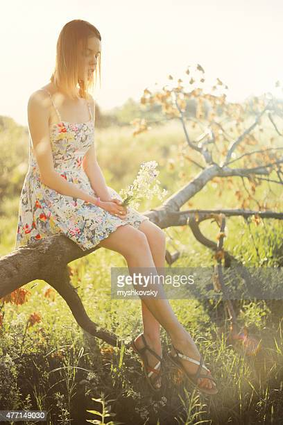 Young woman in dress sitting on the tree