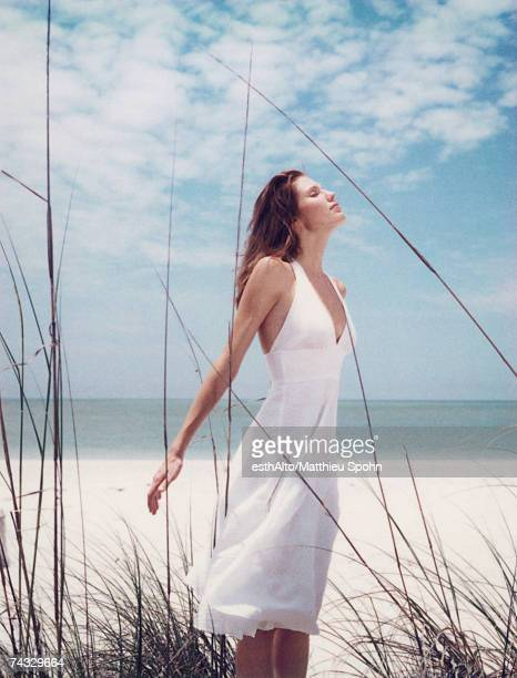 Young woman in dress standing in dune grass with head back, facing wind