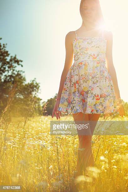 Young woman in dress standing on the grass