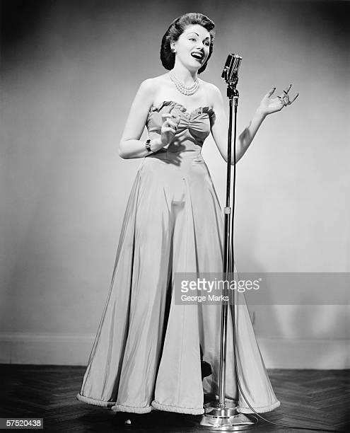 Junge Frau im Abendkleid mit Mikrofon, singen (B & W