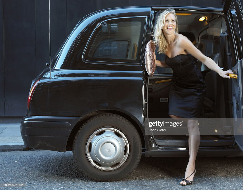 Young woman in evening dress, exiting taxi, smiling