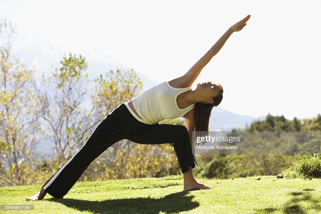 Young woman in extended side angle pose : Stock Photo