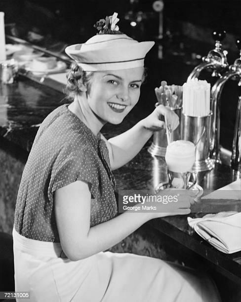若い女性のおしゃれなアイスクリームソーダ飲料の帽子