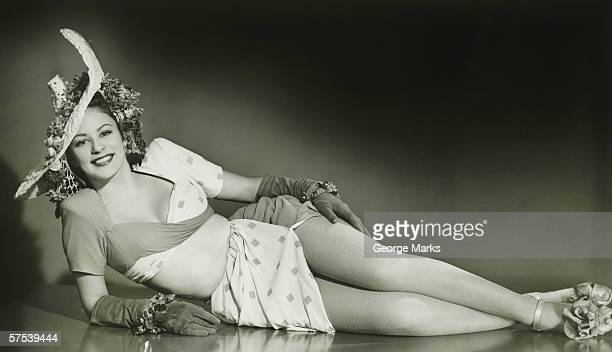 Young woman in fashionable hat lying down in studio, (B&W)