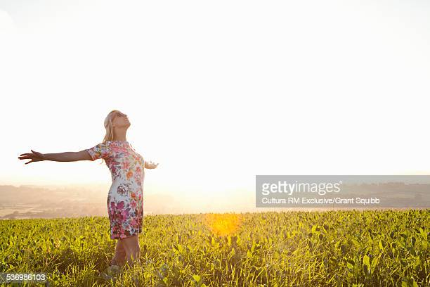 Young woman in field gazing up with arms outstretched, Dorset, England