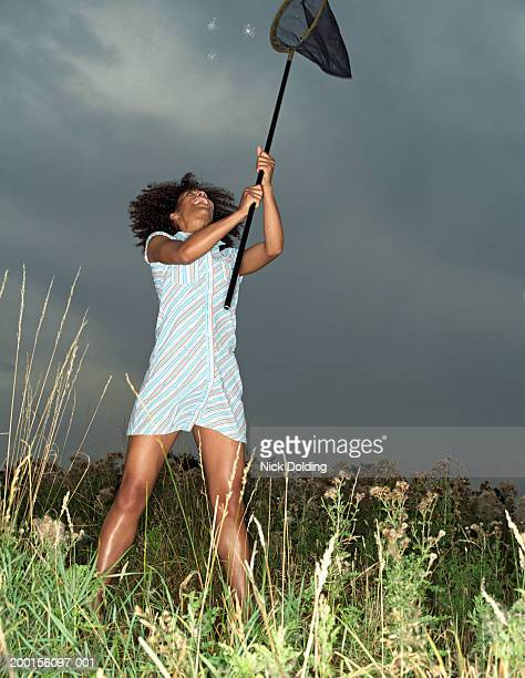 Young woman in field holding up butterfly net towards floating seeds