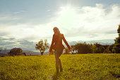 Young woman in field walking away