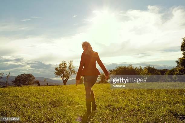 Young woman in field walking away