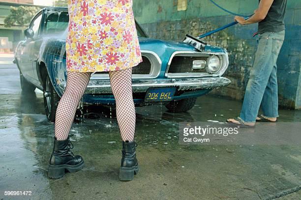 Young Woman in Fishnet Stockings Watching Man Wash Car