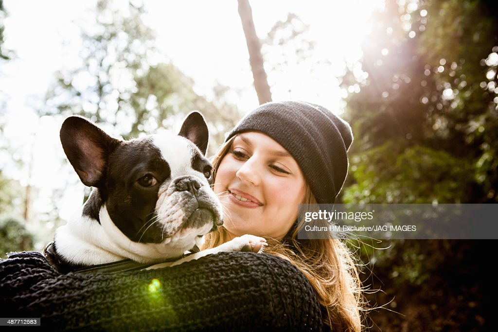 Young woman in forest, holding domestic dog : Stock Photo