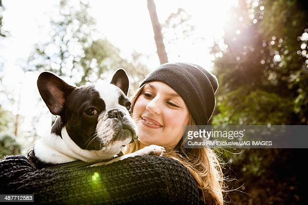 Young woman in forest, holding domestic dog
