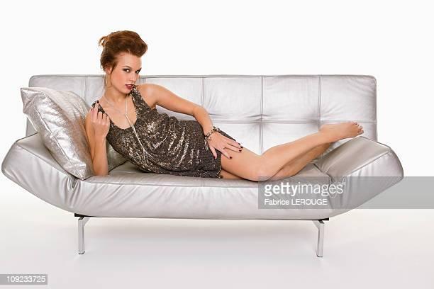 Young woman in formalwear lying on sofa