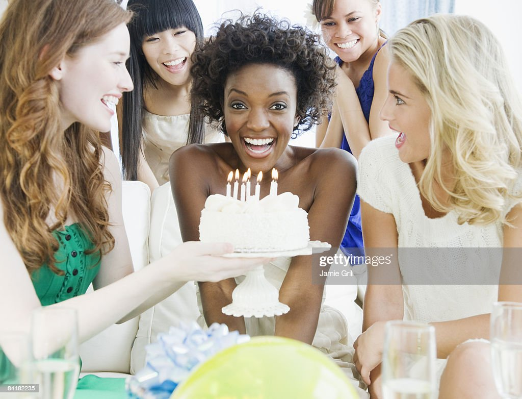 Young woman in front of birhtday cake at party : Stock Photo