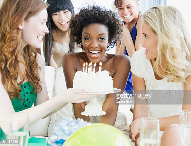 Young woman in front of birhtday cake at party