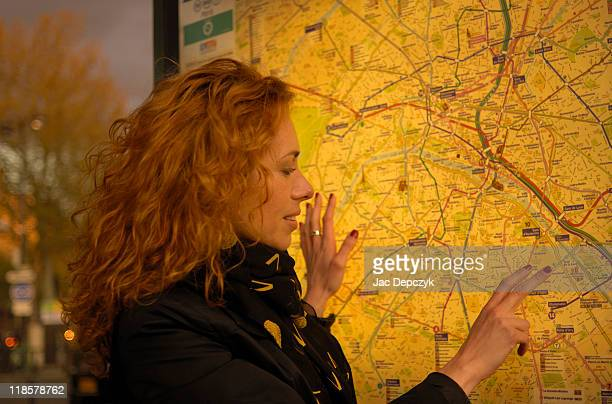 Young woman in front of Paris metro map, evening.