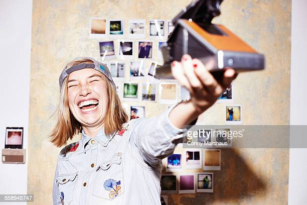 Young woman in front of photo wall taking instant selfie on retro camera