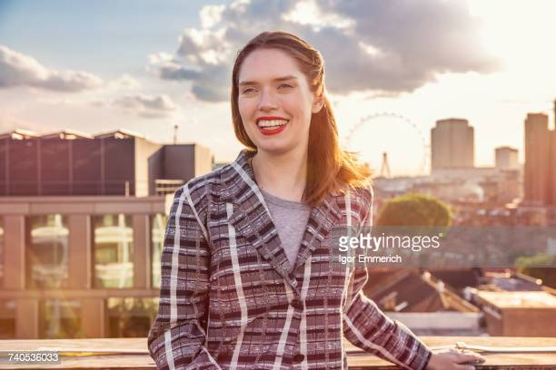 Young woman in front of skyline at roof party in London, UK