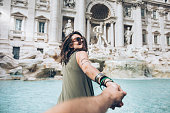 Young woman taking follow me picture in front of Trevi fountain in Rome