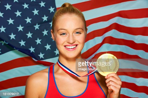 Young woman in front of USA flag with gold medal