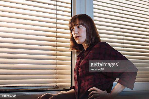 Young woman in front of window, thoughtful