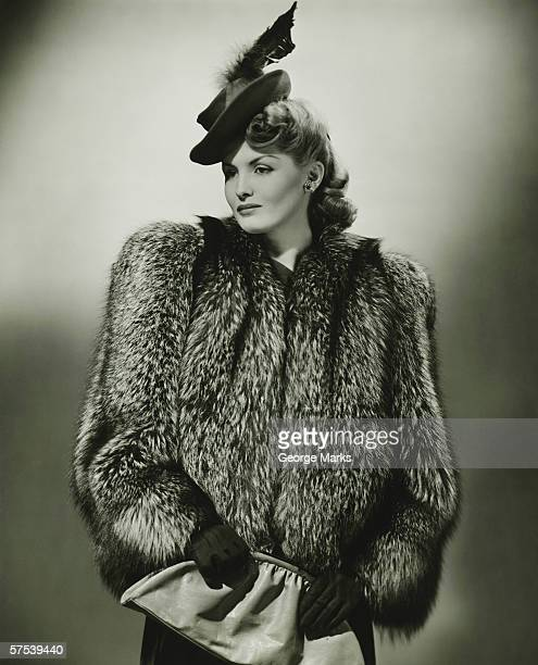 Young woman in fur coat and fashionable hat in studio, (B&W)