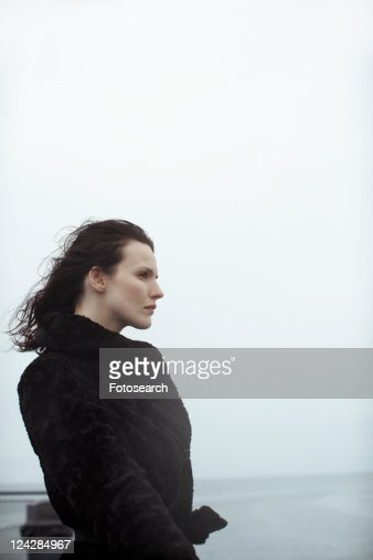 Young woman in fur coat looking at view