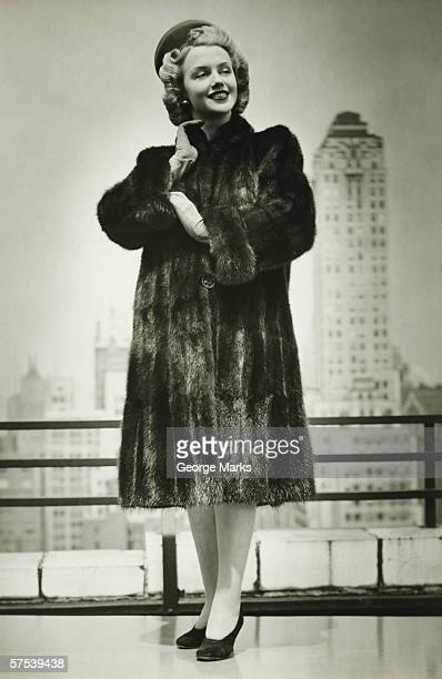 Young woman in fur coat standing outdoors, (B&W)