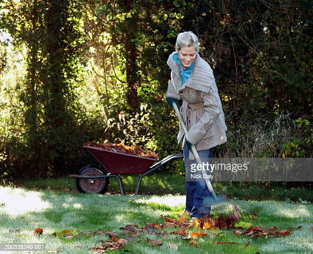 Young woman in garden raking leaves, smiling (blurred motion)