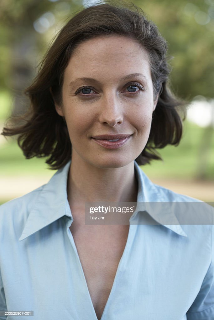 Young woman in garden, smiling, portrait, close-up : Stock Photo