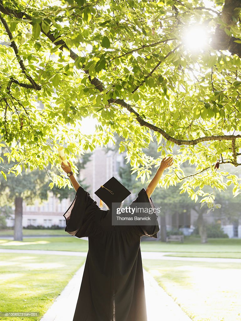 Young woman in graduation gown with raised arms outdoors, rear view
