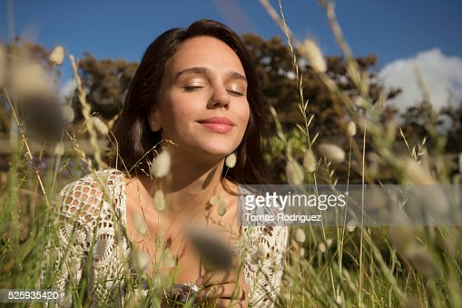 Young woman in grass with eyes closed : Stockfoto