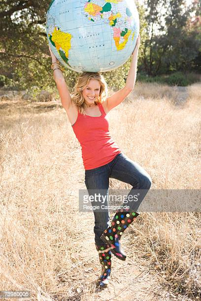Young woman in grassland, holding globe above head, smiling, portrait