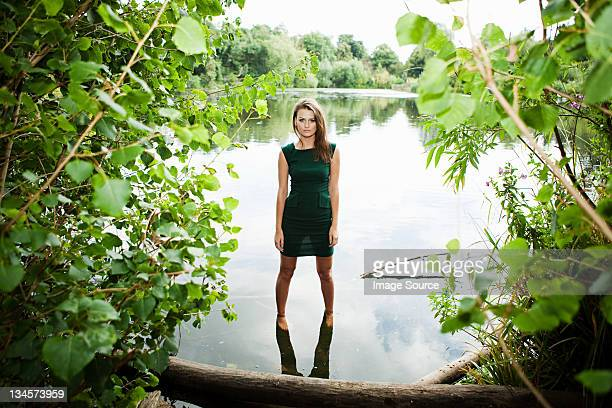 Young woman in green dress, standing in a lake