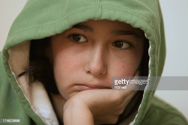 Young woman in green hoodie resting head on hand